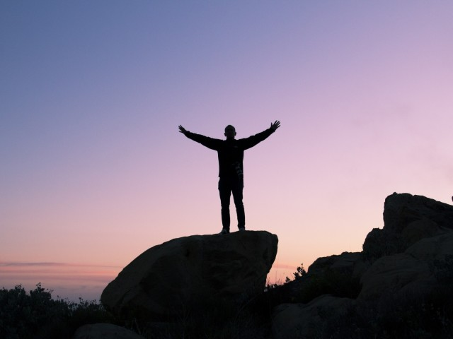 person-silhouette-sunset-rock-boulder-peak